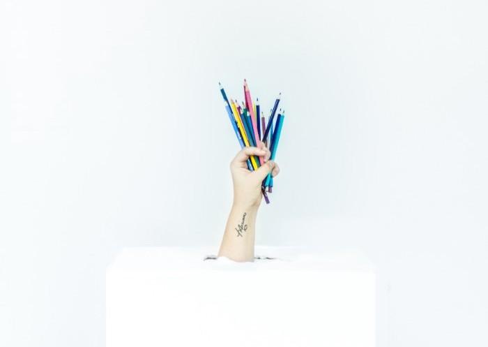 色鉛筆をたくさんつかんで箱から飛び出す手