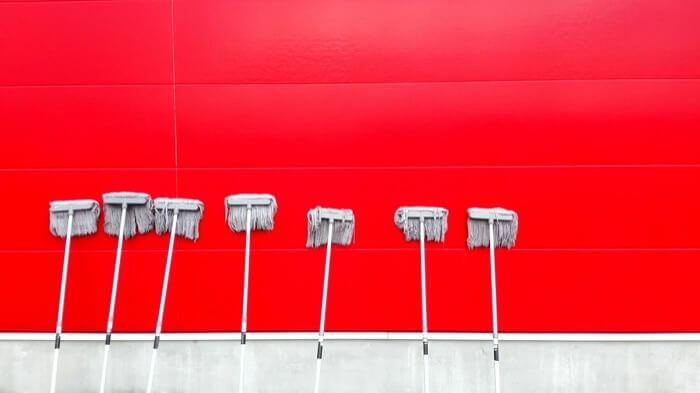 真っ赤な壁に立てかけられた5本のモップ