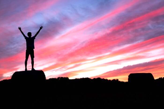 朝焼けの中、頂上で両手を挙げる男性