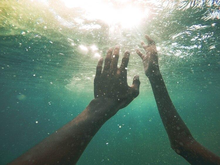 水中から見える光に両手を伸ばす
