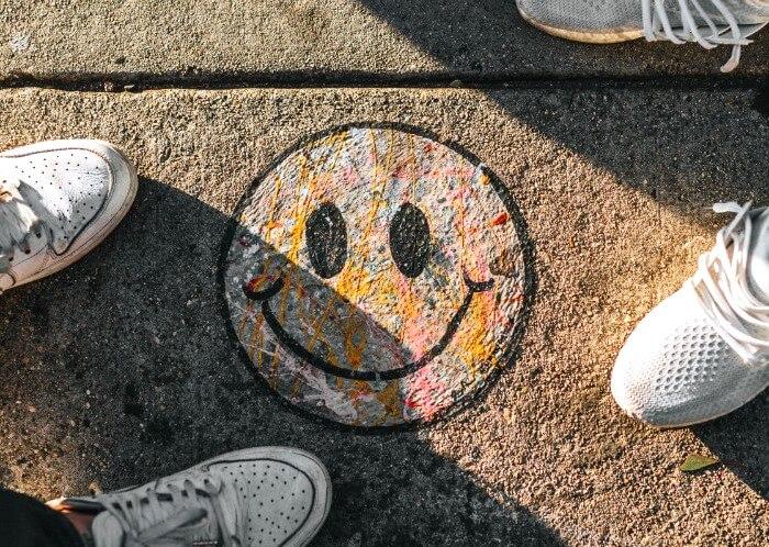 地面に書かれたニコちゃんマークに立つ2人の足