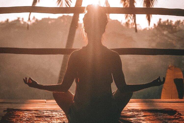 夜明けの中瞑想をする女性