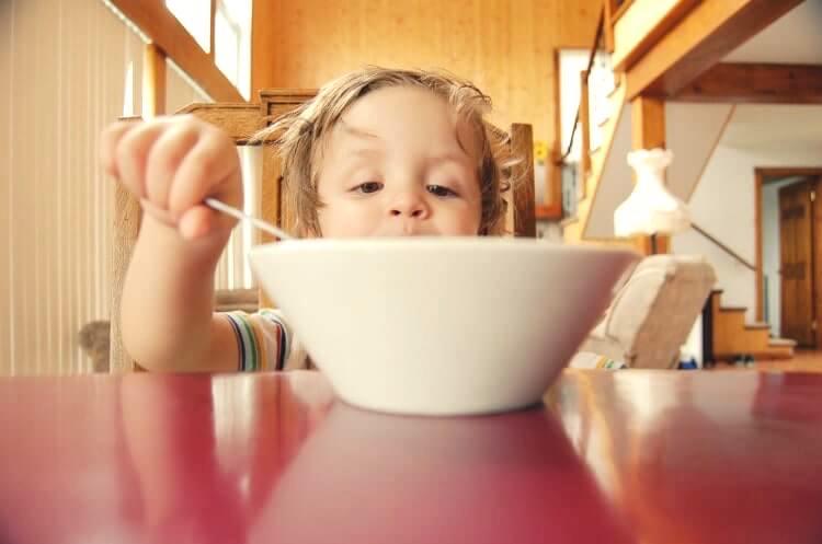 ミルクボウルの中を見ようとする食事中の小さな男の子
