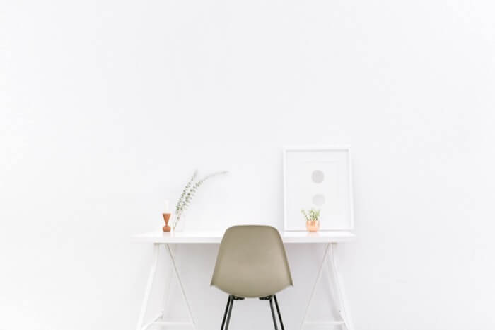 絵画と植物が飾ってある小さな白いテーブルと椅子
