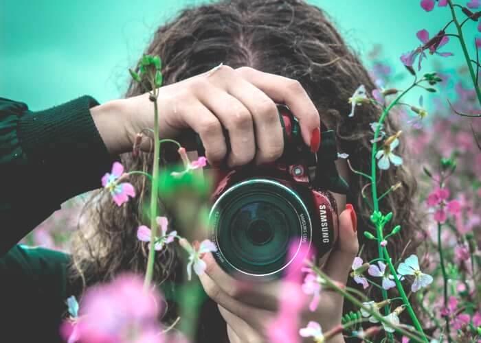 花越しにカメラを構える女性