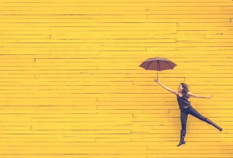 マスタード色の壁と傘で飛べそうな女性