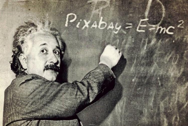 黒板に数式を書くアインシュタイン