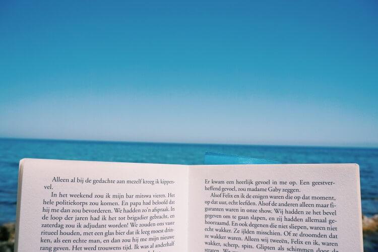 青い空と海を目の前に本を読む