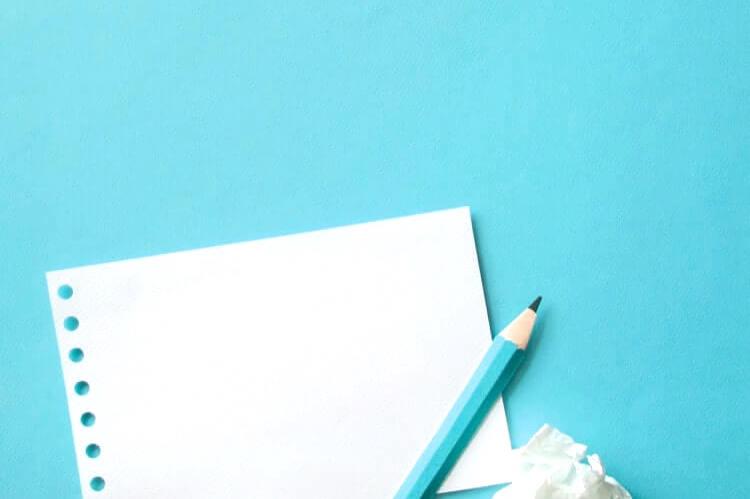 白い紙とターコイズブルーの鉛筆