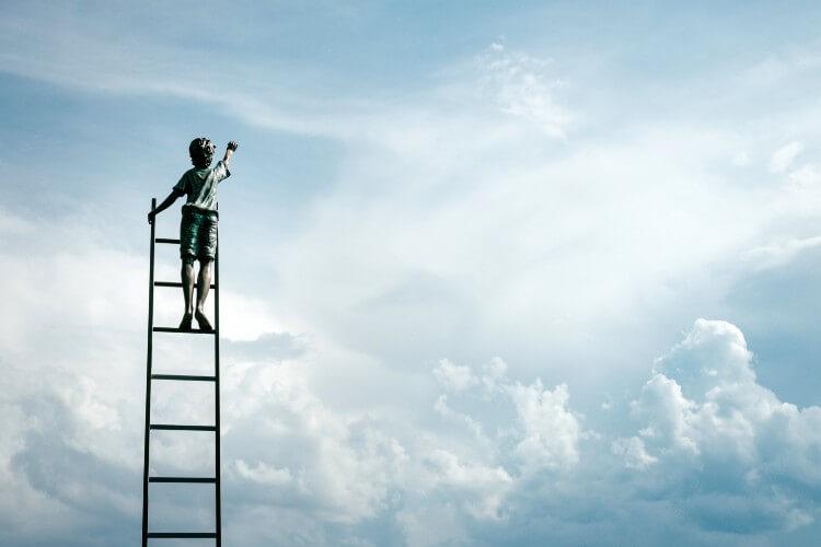 はしごを上って空に手を伸ばす男の子