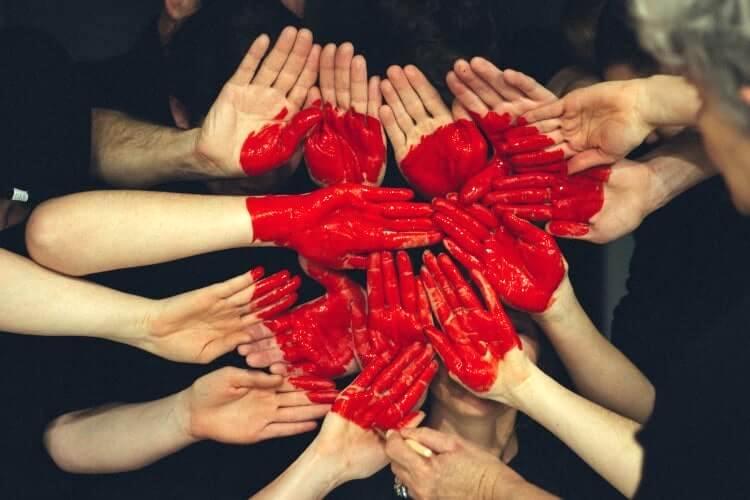赤く塗った手を寄せ集めてハートをつくる