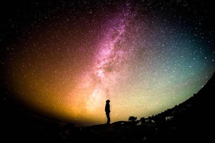 カラフルな宇宙の中に佇む男性