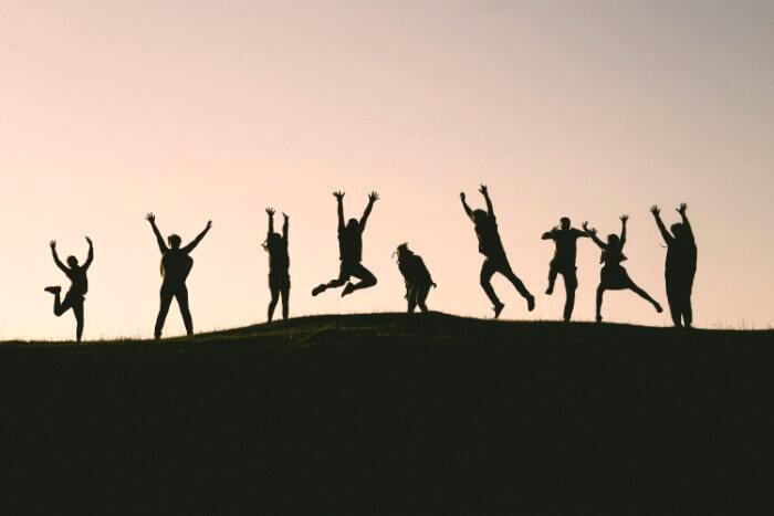 丘の上で飛び跳ねる9人の影